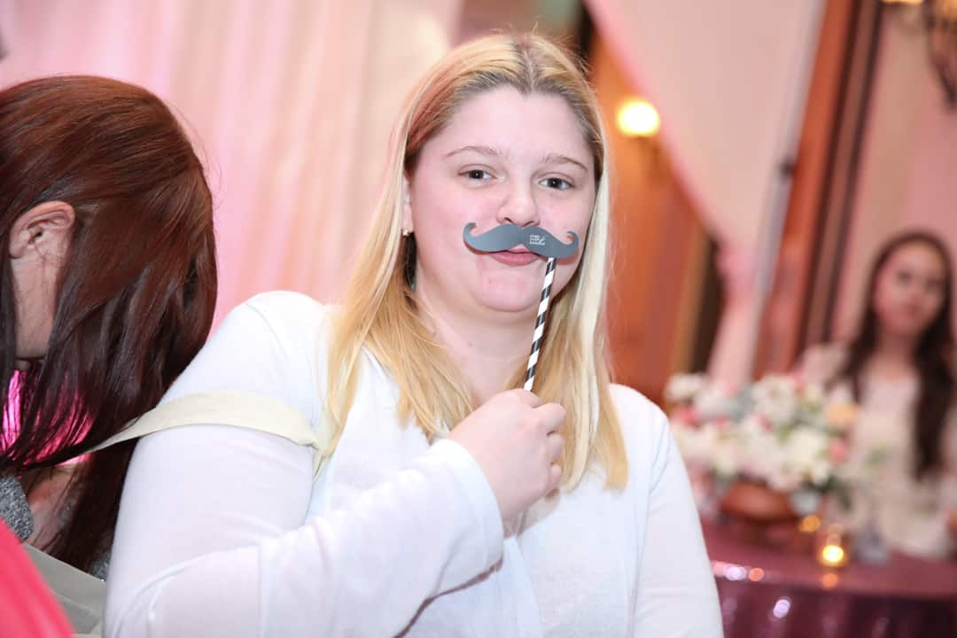 girl holding a photobooth mustache on a stick