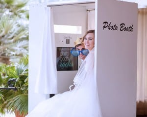 bride and groom peeking out of white classic photo booth