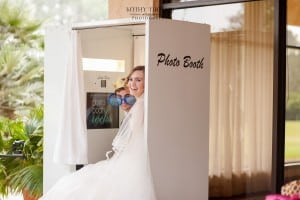 bride and groom peeking out of classic photo booth