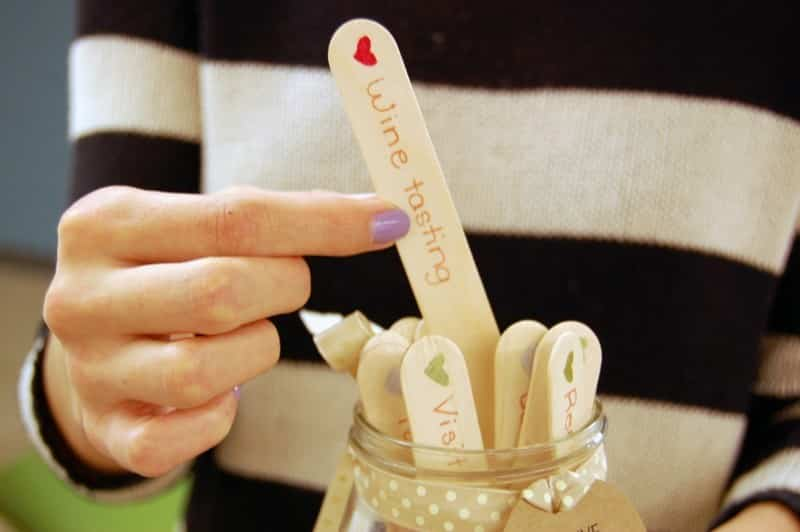 woman's hands picking a popsicle stick out of a jar