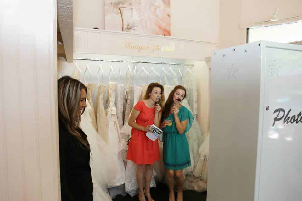 friends posing in photo booth at wedding dress shop