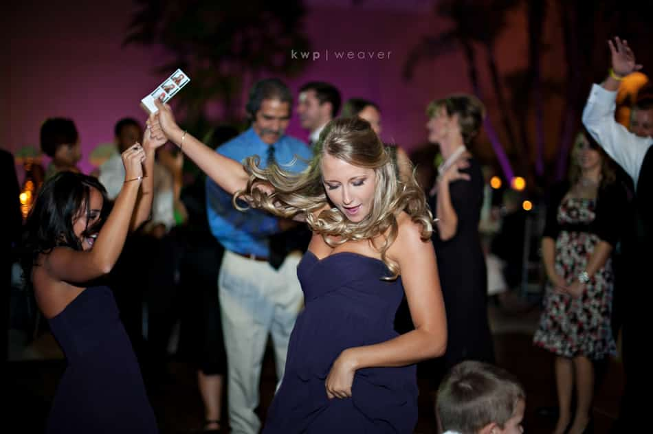 bridesmaid dancing at wedding with photo strip in hand