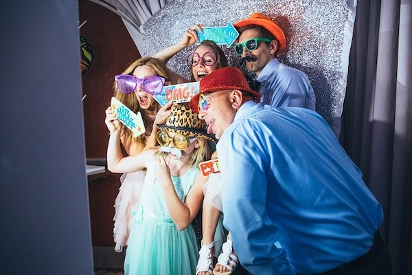 people packed into photo booth with fun props