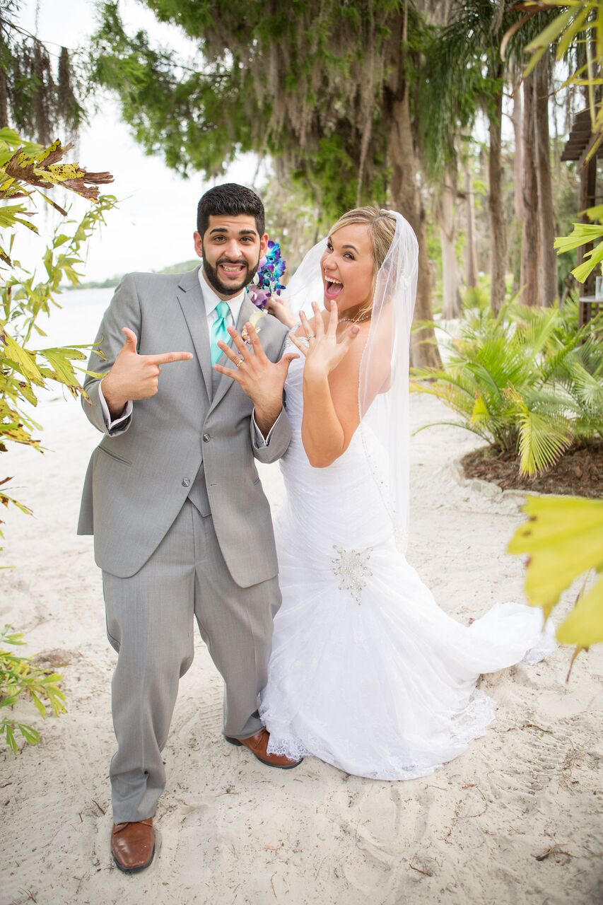 Paradise Cove wedding with black printz booth bride and groom showing off rings
