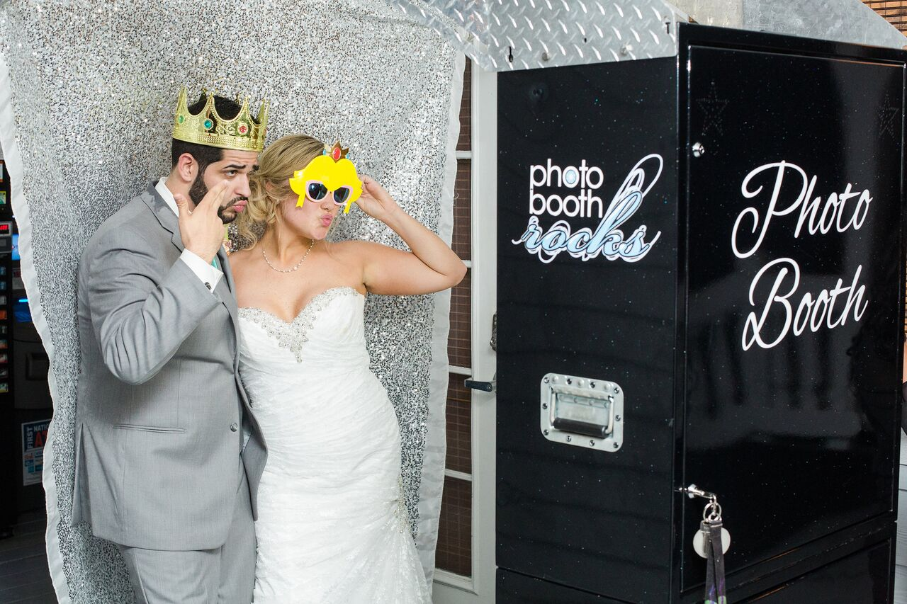 Paradise Cove wedding with black printz booth and silver sparkle backdrop bride and groom pose with props