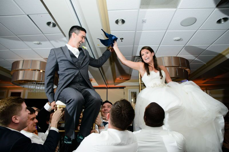 classic white photo booth at Citrus Club wedding bride and groom being lifted in chairs