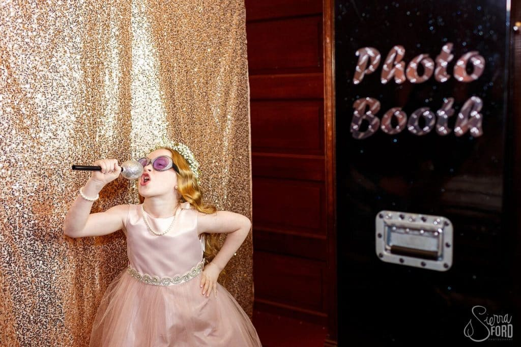little girl posing for photo booth with microphone