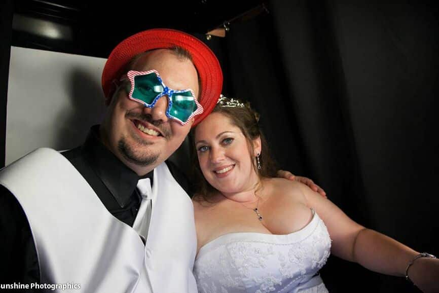 classic black photo booth at The White Room wedding with red, white and blue props
