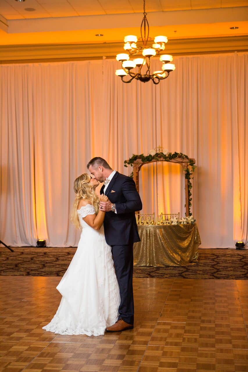 white printz photo booth with gold backrop at Holy Trinity Reception Center wedding bride and groom kissing