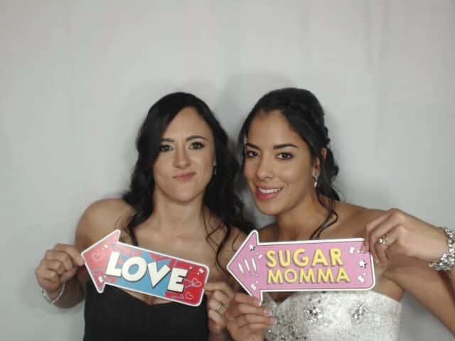 brides posing in white printz photo booth at wedding