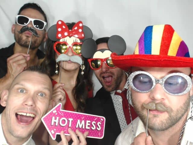 guests posing with props in white printz photo booth at wedding