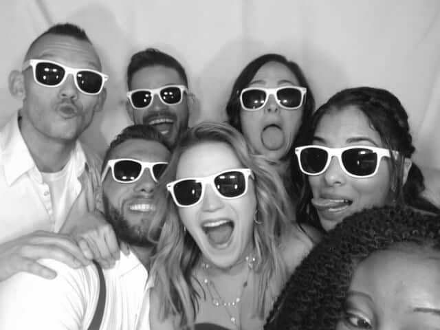 black and white image of crowded photo booth with people in sunglasses