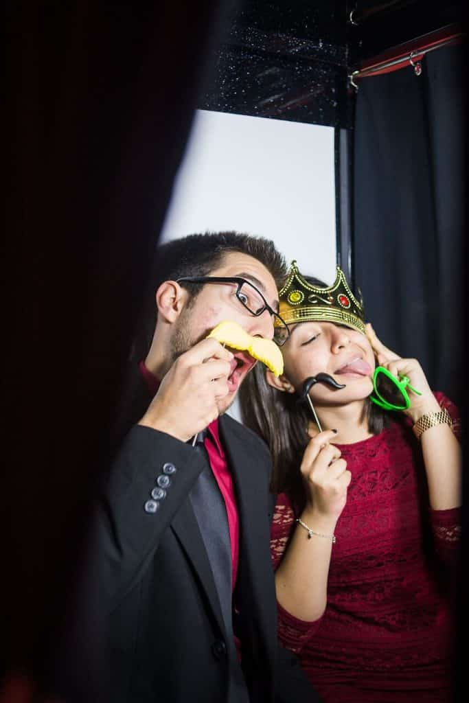 Couple posing in photo booth with fake mustaches