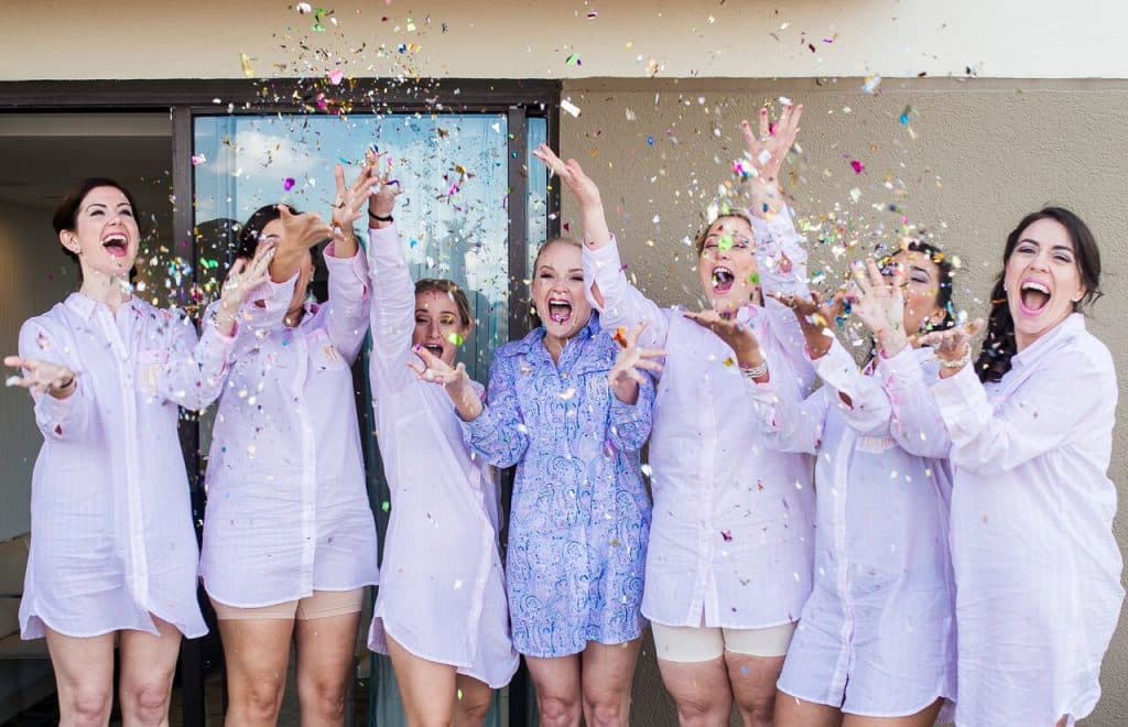 bridal party in men's shirts throwing glitter