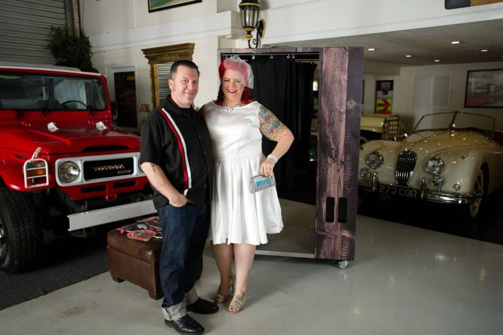 rockabilly bride and groom with wood photo booth