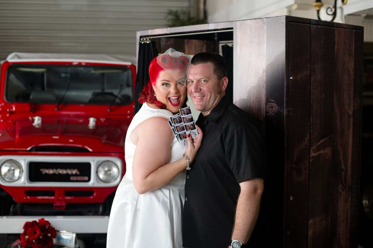 bride and groom showing off photo strips from new classic wooden photo booth from Photo Booth Rocks at wedding