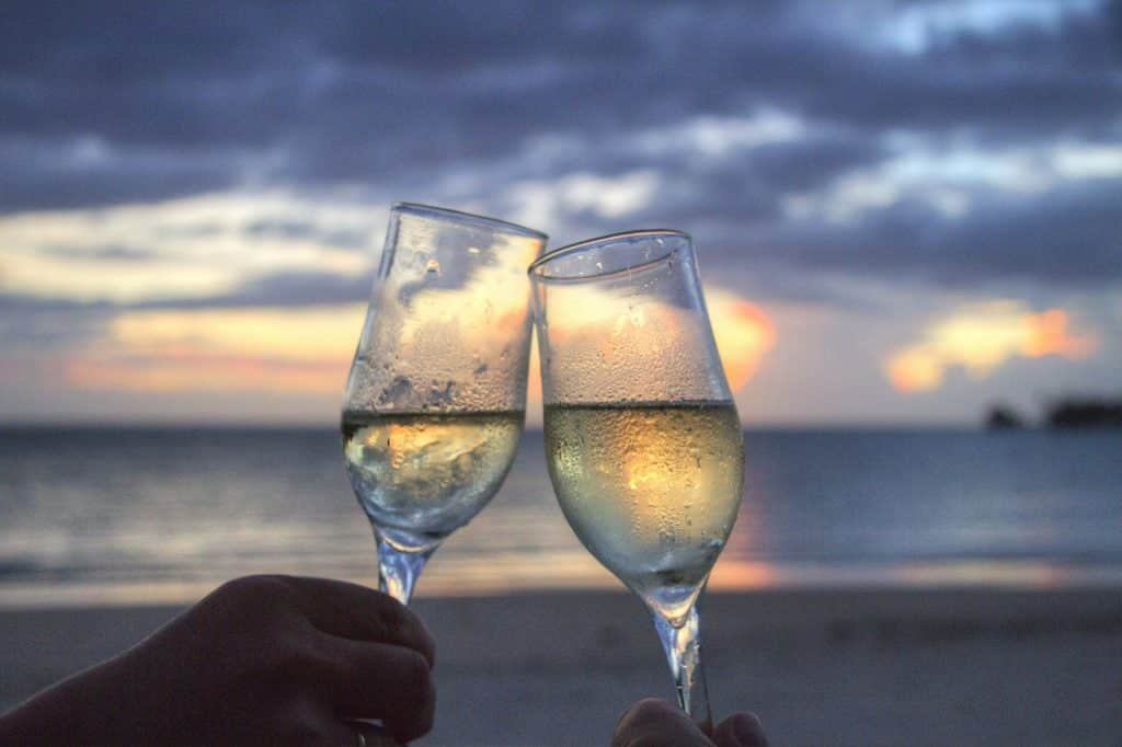 two champagne glasses toasting on beach
