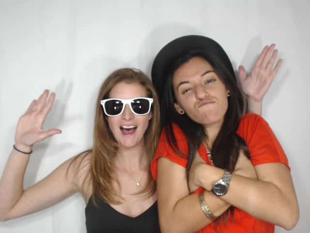 two girls posing with hat in photo booth