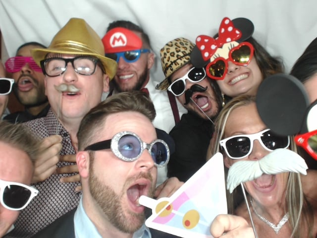 large group in photo booth with sunglasses props
