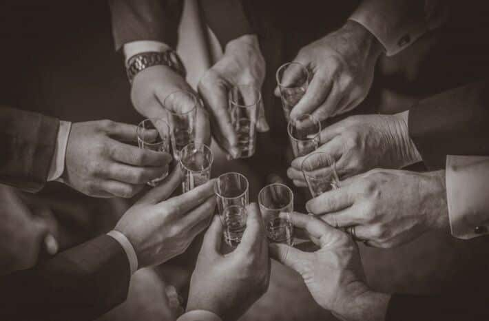 groomsman's hands holding shot glasses in a circle