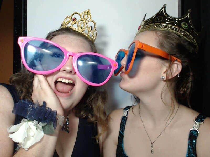 teens wearing fun props in photo booth