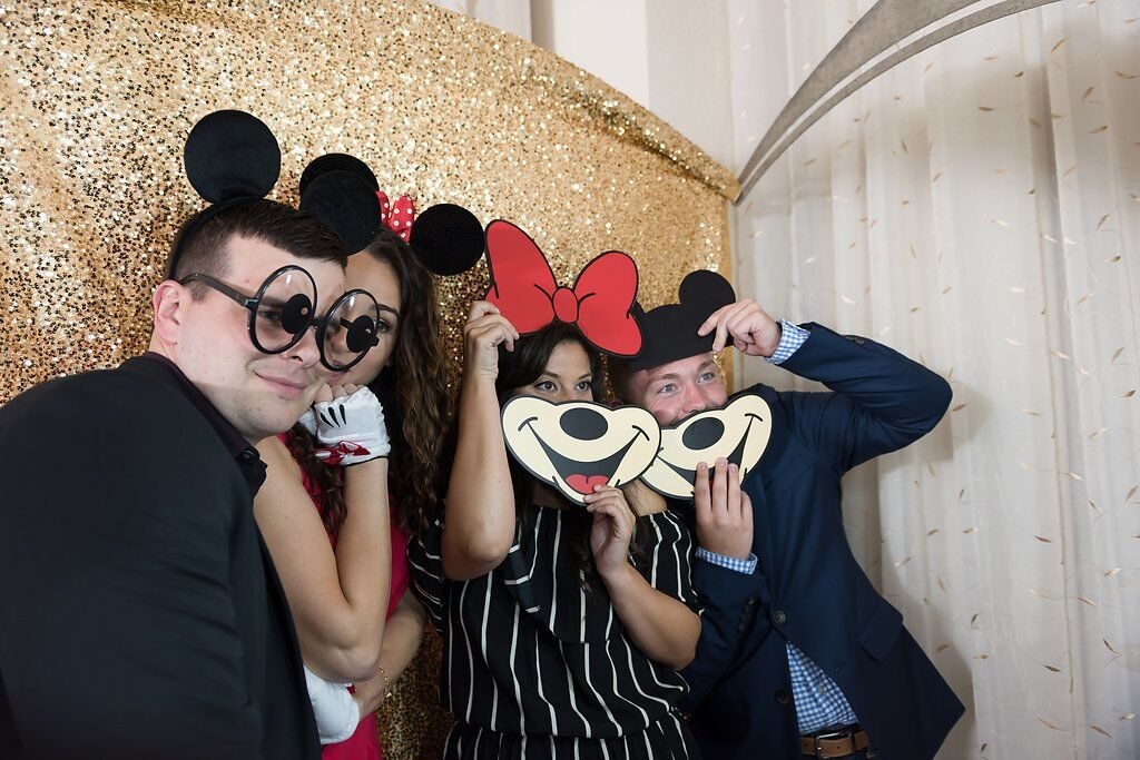 wedding guests posing with disney themed props