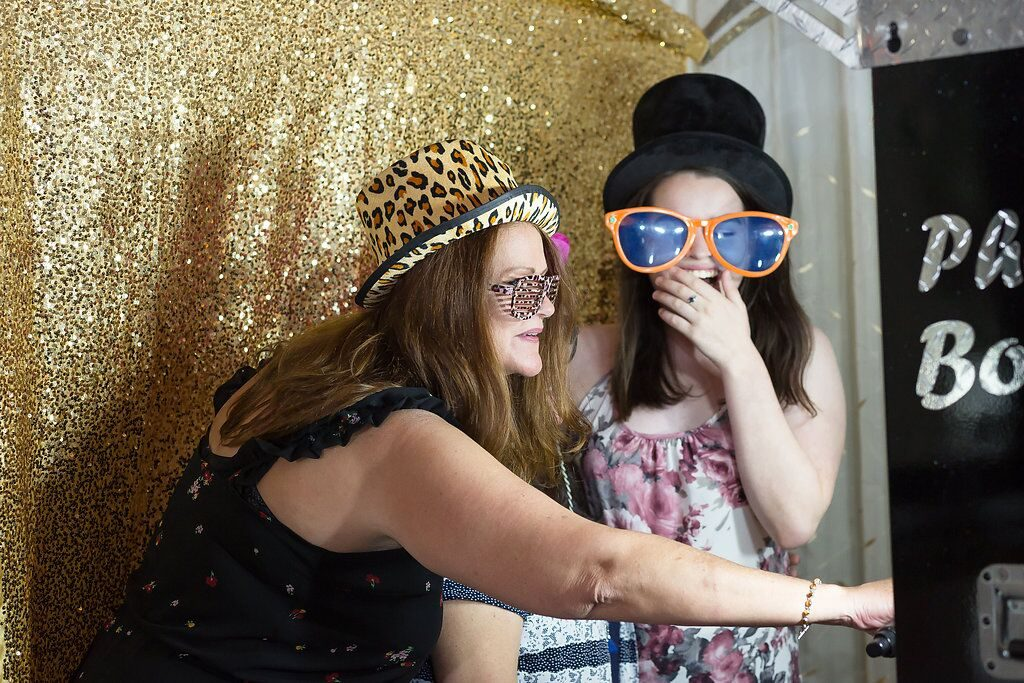wedding guests laughing in photo booth gold glitter backdrop