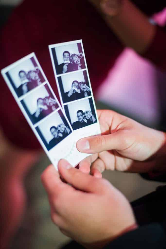 hands holding photo booth strips