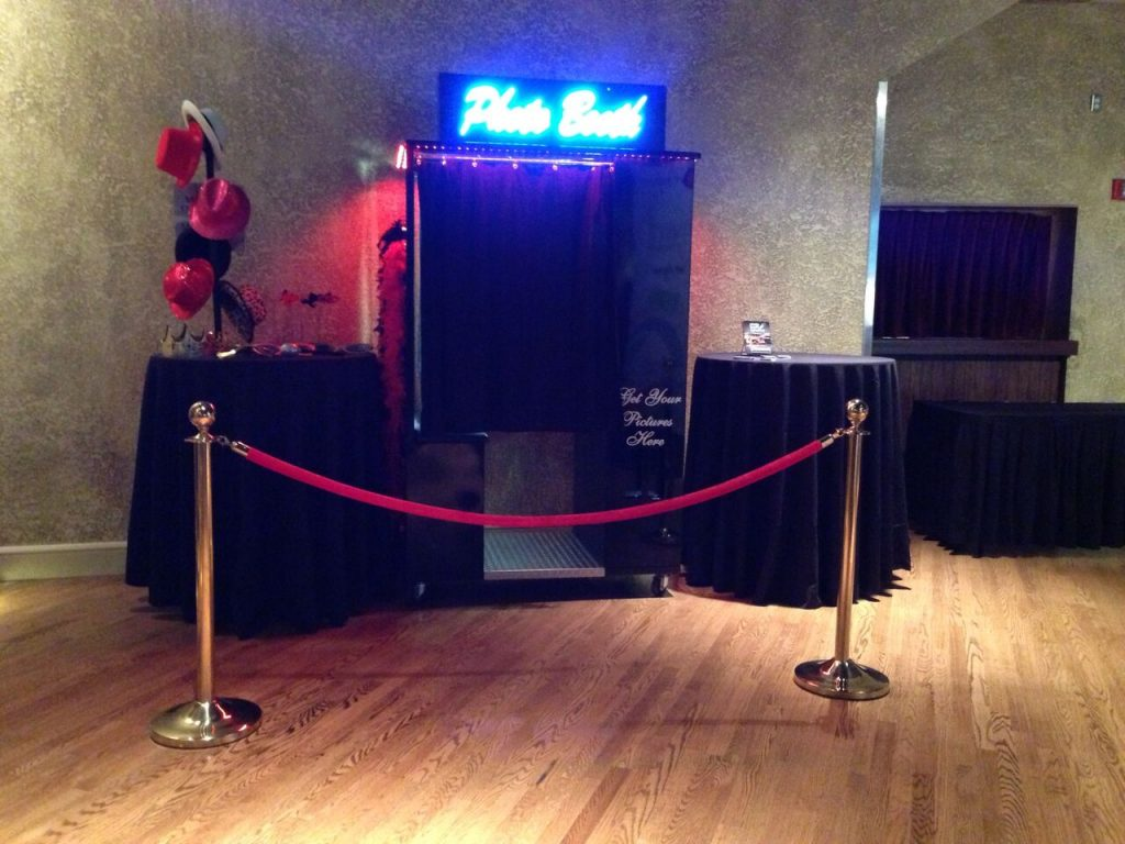 photo booth with neon sign and red velvet ropes