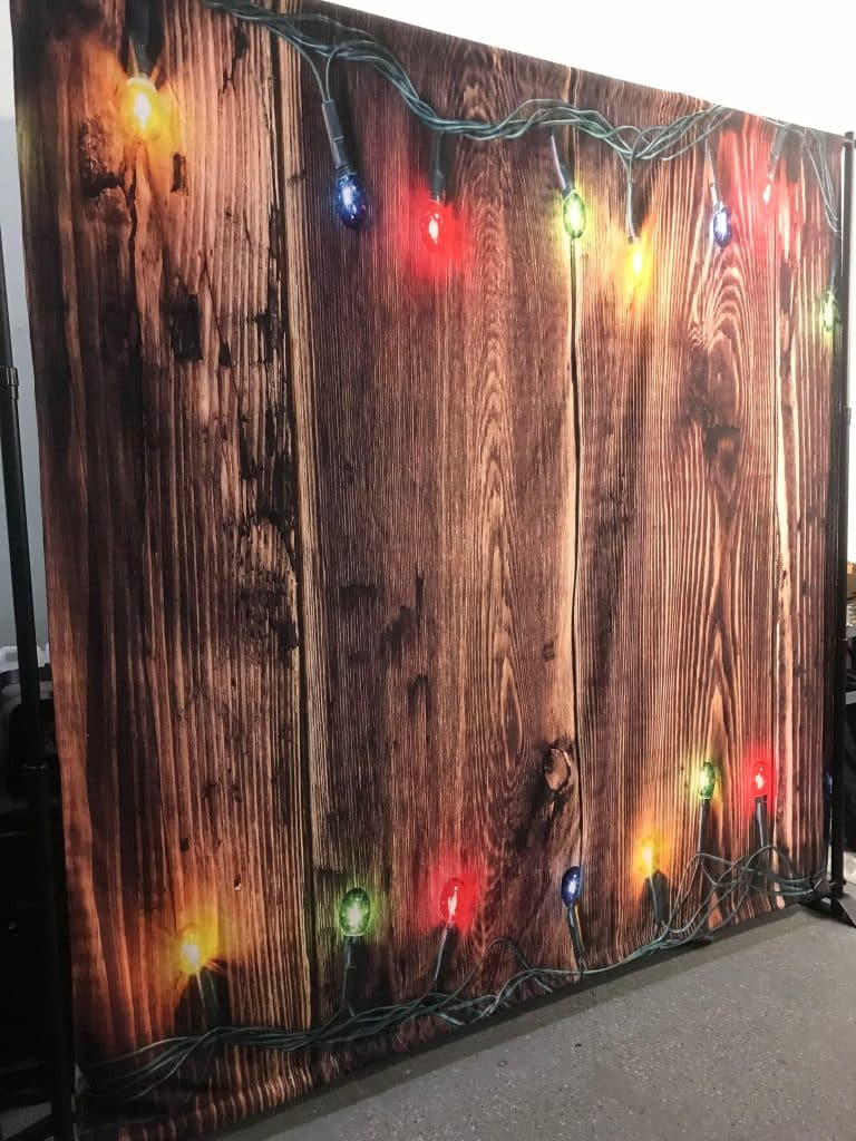 large fabric backdrop with rustic wood print and christmas lights