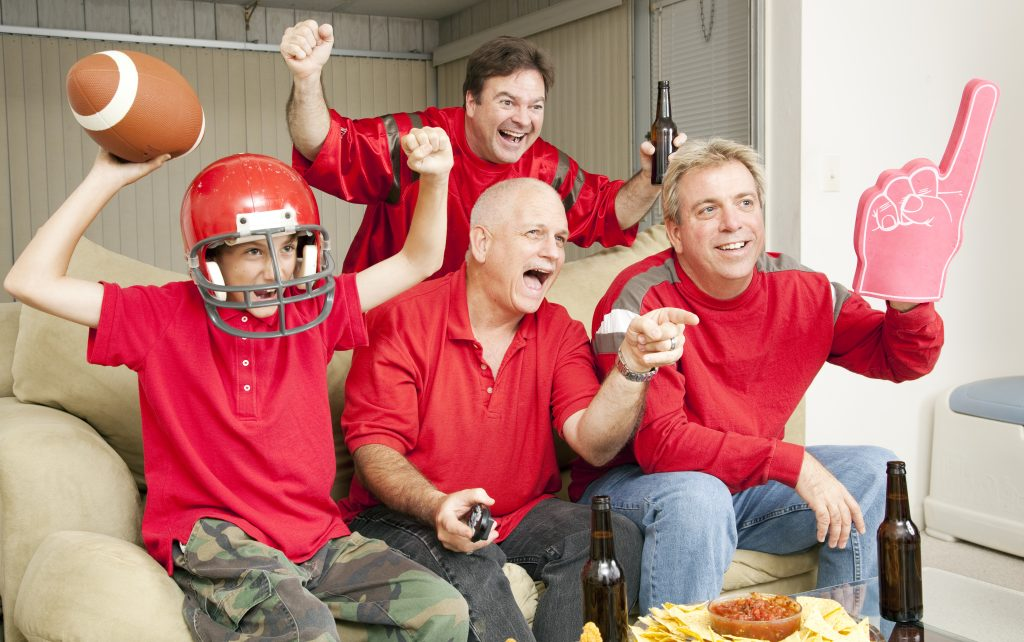 football fans cheering at tv from couch