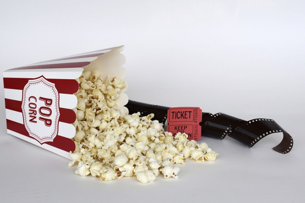 box of popcorn spilling next to tickets and roll of film