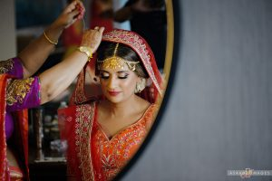 Indian bride Rena having her sari veil put on