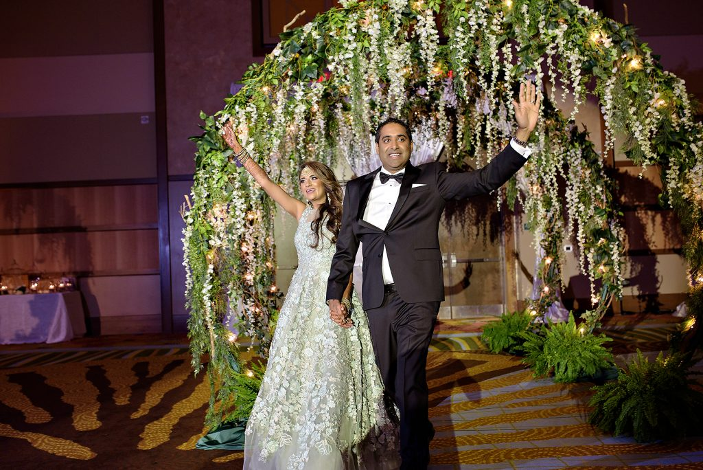Rena and Shanthan walking through floral archway into wedding reception