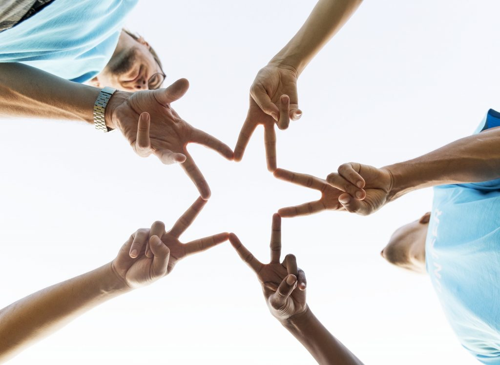 five people holding fingers together in a star shape