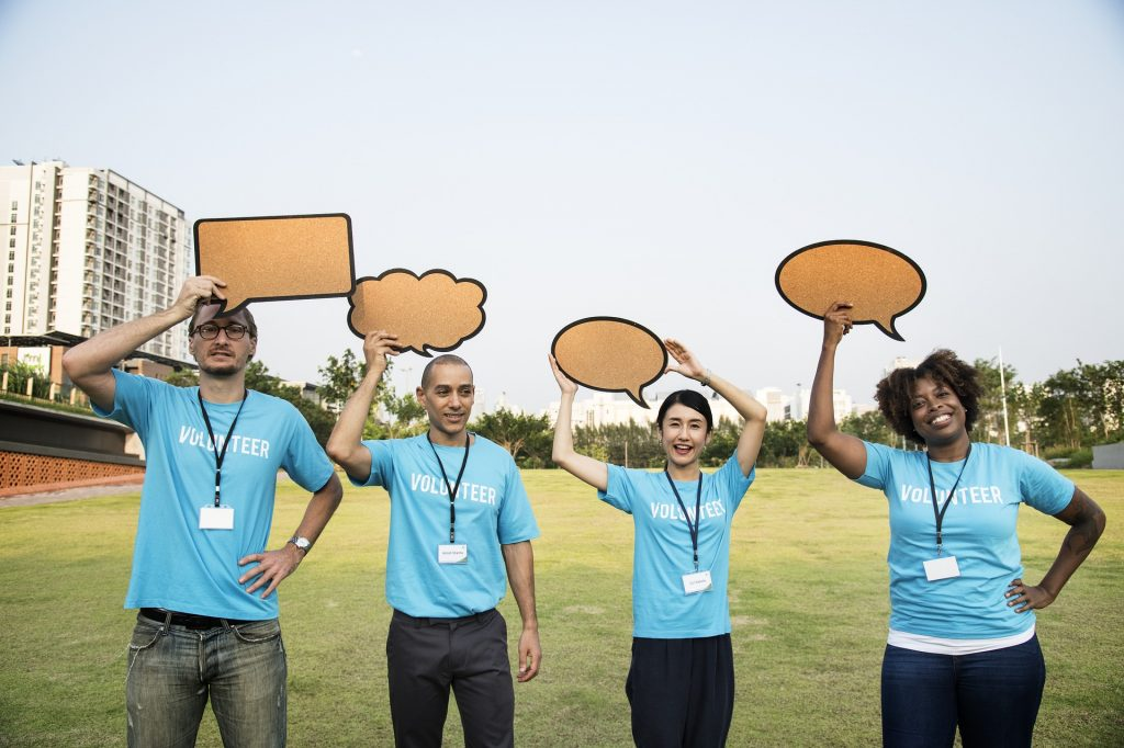 people wearing volunteer shirts holding blank speech bubbles over their heads